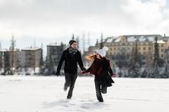 Young joyful couple enjoying the winter season. Couple having fun in Tatra mountains, Slovakia Royalty Free Stock Image