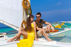 Couple having fun on tropical beach on the sailboat. Summer vaca Royalty Free Stock Photography