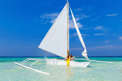 Couple having fun on tropical beach on the sailboat. Summer vaca Royalty Free Stock Photo