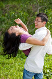 Couple having fun in the tropical garden. Happy young Asian couple having fun with the guy carrying the girl Royalty Free Stock Images