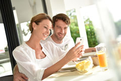 Couple having fun using smartphone and eating breakfast Stock Photo