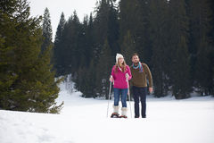 Couple having fun and walking in snow shoes Royalty Free Stock Photography
