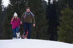 Couple having fun and walking in snow shoes Stock Photography