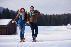 Couple having fun and walking in snow shoes Stock Photos