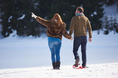 Couple having fun and walking in snow shoes Royalty Free Stock Image