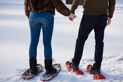 Couple having fun and walking in snow shoes Stock Image