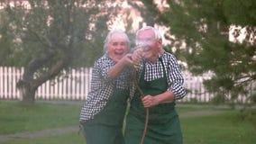 Couple having fun, water hose.