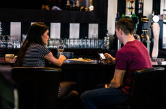 Couple having a glass of wine while man is texting Stock Images