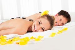 Couple having a hot stone massage Stock Images