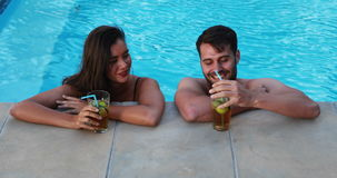 Couple having iced tea while interacting at poolside. On a sunny day stock video footage