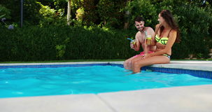 Couple having iced tea while interacting at poolside. On a sunny day stock video