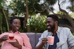 Couple having lemon tea and black coffee in garden. Happy couple having lemon tea and black coffee in garden Stock Images