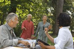 A couple having lunch, another couple joining them. Stock Image