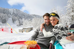 Couple having a lunch break on the skiing slopes Stock Photos