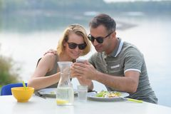Couple having lunch outdoors by lake Stock Photos