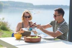 Couple having marvellous brunch near lake Stock Photo