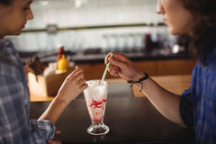 Couple having milkshake at counter. In restaurant Royalty Free Stock Photos