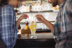 Couple having milkshake at counter. In restaurant Royalty Free Stock Images