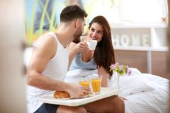 Couple having morning breakfast in bed royalty free stock photo