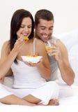 Couple having nutritive breakfast in bed. Happy couple having nutritive breakfast in bed Stock Images