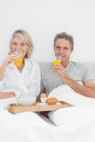 Couple having orange juice at breakfast in bed Royalty Free Stock Photography