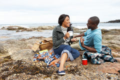 Couple having picnic on beach Royalty Free Stock Photos