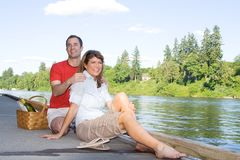 Couple Having a Picnic by the Lake - Horizontal royalty free stock photography