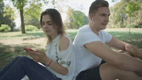 Young couple listening to music outdoor. Couple having picnic at the park. Lovers relax together. The girl put in ear headphone and give another to the boy stock video footage