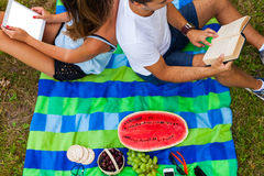 Couple having picnic. Pretty girl reads. Man is using tablet Royalty Free Stock Photography
