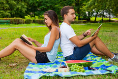 Couple having picnic. Pretty girl reads. Man is using tablet Royalty Free Stock Images