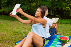 Couple having picnic. Pretty girl is taking selfie, Man reads Royalty Free Stock Photos