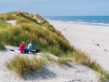 Couple having picnic on sand dune looking over beach and North Sea on West Frisian island Ameland, Friesland, Netherlands stock photography
