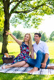 Couple having picnic on summer meadow. Couple, men and woman, having picnic on summer meadow Stock Image