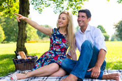 Couple having picnic on summer meadow. Couple, men and woman, having picnic on summer meadow Stock Photos