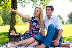 Couple having picnic on summer meadow Stock Photos