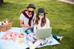 Couple having picnic and using laptop in park Royalty Free Stock Image