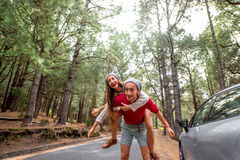 Couple having piggyback ride in the forest Stock Photo