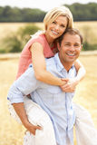 Couple Having Piggyback In Summer Harvested Field royalty free stock image
