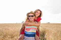 Couple Having Piggyback In Summer Harvested Field Stock Photo