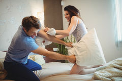 Couple having a pillow fight on bed. In bedroom stock photography