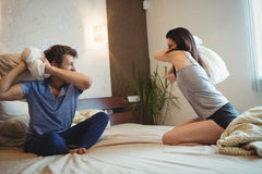 Couple having a pillow fight on bed. In bedroom stock photo