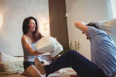 Couple having a pillow fight on bed. In bedroom royalty free stock image