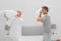 Couple having a pillow fight. At home in bedroom stock image