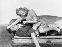 Couple having a playful fight on a couch royalty free stock photos