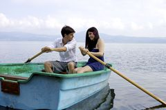Couple having problem rowing boat on lake Royalty Free Stock Photo