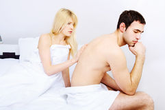 Couple having problems, focus on female. Young couple having problems in bedroom, focus on female Royalty Free Stock Images