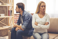 Couple having a quarrel. Beautiful couple is sitting back to back on the couch while having a quarrel Stock Photo