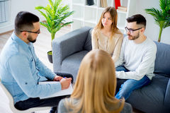 Couple having a quarrel on a therapy. Beautiful couple is sitting while having a quarrel Royalty Free Stock Photos