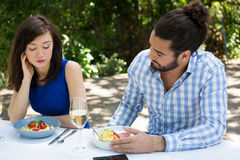 Couple having relationship difficulties at restaurant. Young couple having relationship difficulties at outdoor restaurant Royalty Free Stock Image