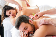 Couple having relaxing body massage in spa. Two therapists doing back massage on couple at the same time Royalty Free Stock Photography